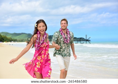 Happy couple having fun running on Hawaii beach vacations in Hawaiian clothing wearing Aloha shirt and pink sarong sun dress and flower leis for traditional wedding or honeymoon concept.