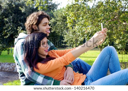 Happy couple having fun taking picture with mobile phone in park - stock photo