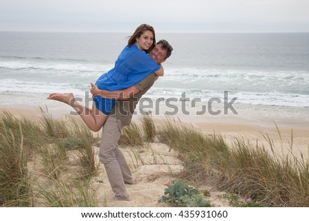 Happy couple having fun together at the beach freedom - stock photo