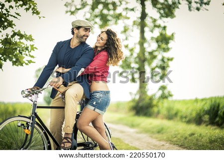 Happy couple having fun while biking on a country road - stock photo