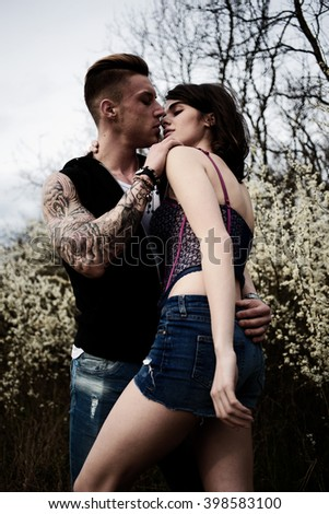 Happy couple having great time together. Attractive sexy woman leaning on the bare chest of attractive young brunette man. Fashion photo. - stock photo