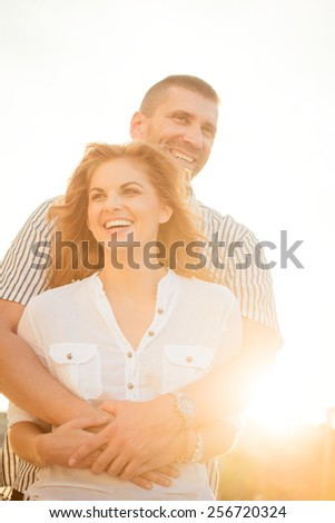 Happy couple having great time together - photographed at sunset against sun - stock photo