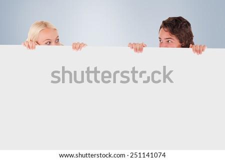 Happy couple hiding against grey vignette - stock photo