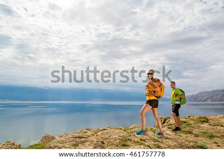 Happy couple hikers trekking in summer mountains on island seaside. Young woman and man walking with backpack on rocky mountain trail. Camping and looking at beautiful inspirational landscape view.