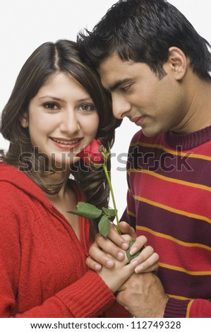 Happy couple holding a flower - stock photo
