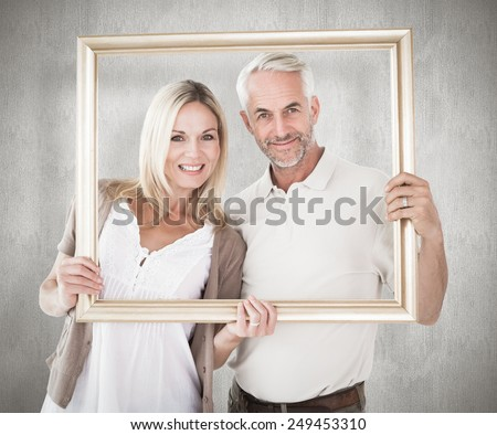 Happy couple holding a picture frame against weathered surface - stock photo