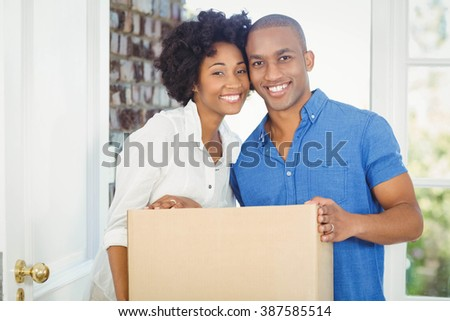 Happy couple holding box out of their house - stock photo