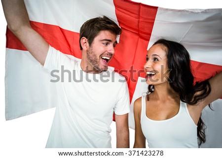 Happy couple holding England flag on white screen - stock photo