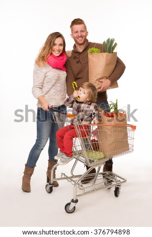 Happy couple holding grocery shopping bags while their little baby sitting in shopping cart isolated on white background. - stock photo