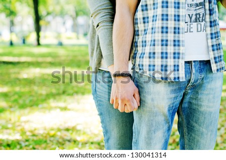 Happy couple holding hands against green background - stock photo