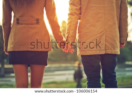 Happy couple holding hands looking in the sunset - stock photo