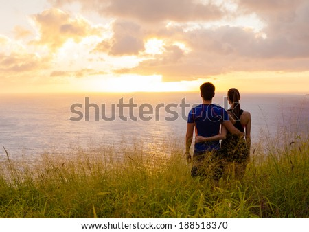 Happy couple holding hands looking in the sunset/sunrise. - stock photo