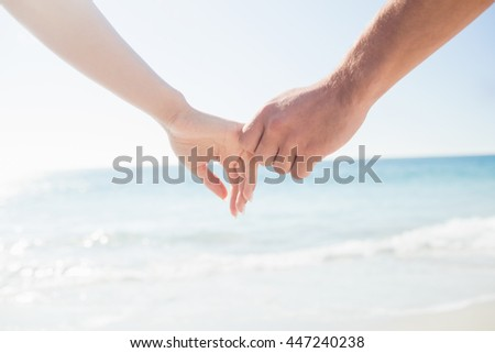 happy couple holding hands on the beach