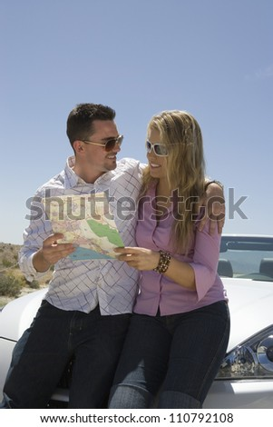 Happy couple holding map and looking at each other - stock photo