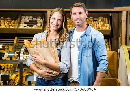 Happy couple holding paper bag in grocery store