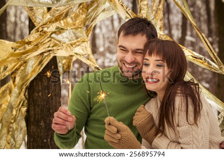 happy couple holding sparklers - stock photo