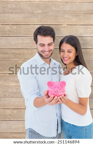 Happy couple holding their piggy bank against wooden planks - stock photo