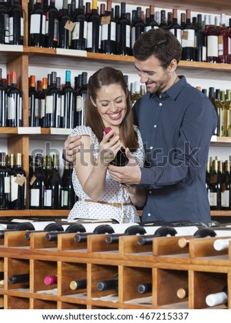 Happy Couple Holding Wine Bottle In Shop