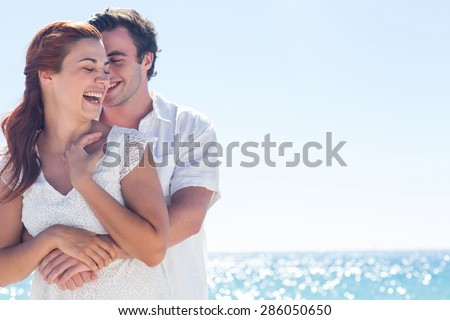 Happy couple hugging and laughing together at the beach - stock photo