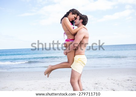 Happy couple hugging and looking at each other at the beach - stock photo