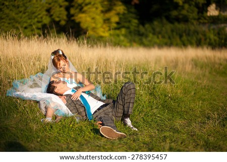 happy couple hugging and lying in the grass on background forest