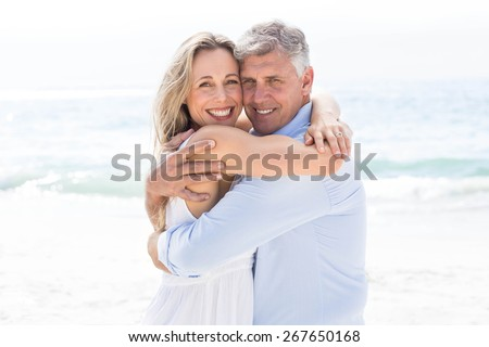 Happy couple hugging each other and looking at camera at the beach