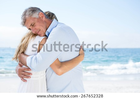 Happy couple hugging each other at the beach - stock photo