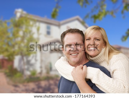 Happy Couple Hugging In Front of a Beautiful House.