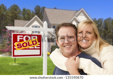 Happy Couple Hugging in Front of Sold Real Estate Sign and House.