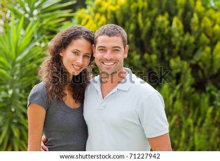 Happy couple hugging in the garden - stock photo
