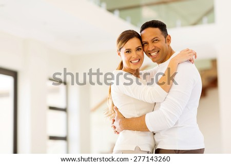 happy couple hugging in their new house - stock photo