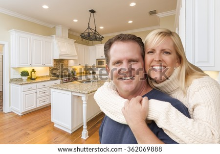 Happy Couple Hugging Inside Beautiful Custom Kitchen. - stock photo