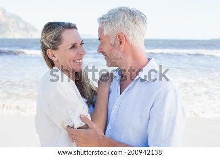 Happy couple hugging on the beach looking at each other on a sunny day - stock photo