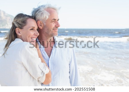 Happy couple hugging on the beach looking out to sea on a sunny day - stock photo