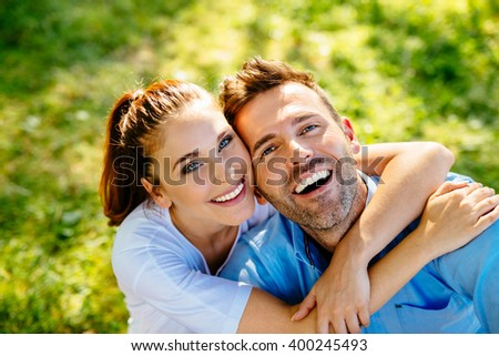 Happy couple hugging, sitting on grass in park