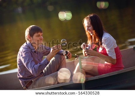 happy couple in a boat bubble blowers - stock photo