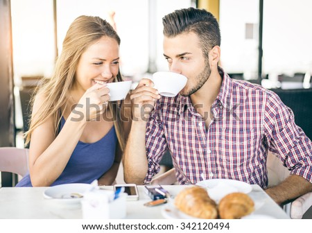Happy couple in a coffee house having breakfast - Pretty lovers in a restaurant looking each others in the eyes - stock photo
