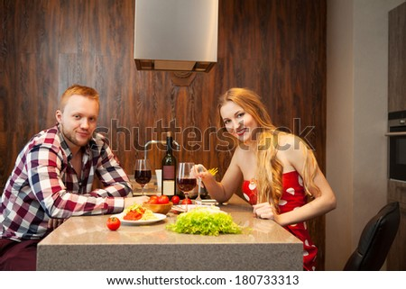 Happy couple in a kitchen eating pasta and drinking red wine in a kitchen