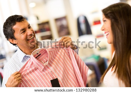 Happy couple in a store shopping for shirts - stock photo
