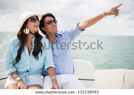 Happy couple in a yacht enjoying the summer and pointing
