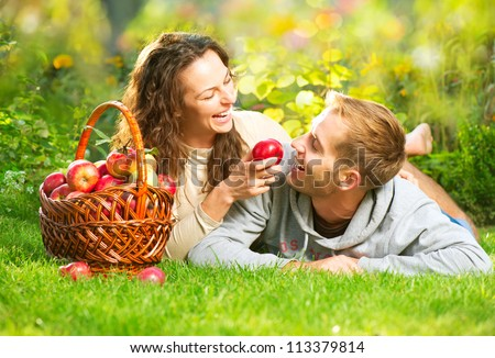 Happy Couple in Autumn Garden.Having Fun on the Grass and Eating Apples Healthy Food.Outdoor.Park.Basket of Apples.Harvest concept. Diet - stock photo
