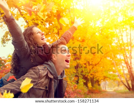 Happy Couple in Autumn Park. Fall. Young Family Having Fun Outdoors. Yellow Trees and Leaves. Laughing Man and Woman outside. Freedom Concept. - stock photo
