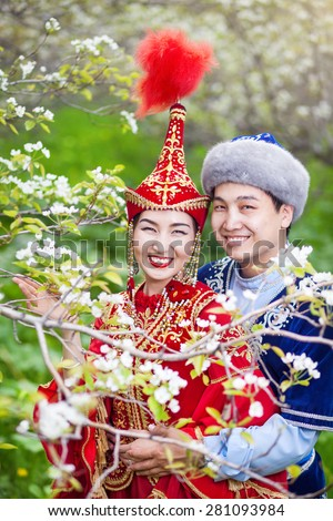 Happy couple in Kazakh costumes in Spring Blooming apple garden of Almaty, Kazakhstan, Central Asia - stock photo