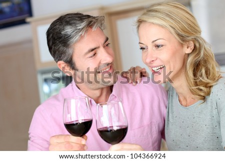 Happy couple in kitchen drinking red wine - stock photo