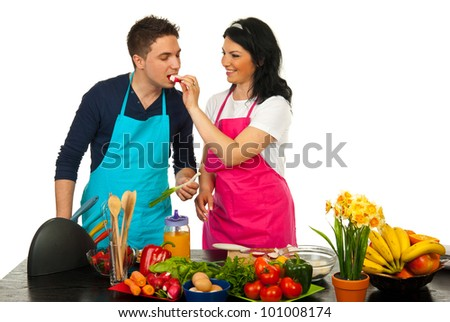 Happy couple in kitchen,woman giv ing man to eat vegetables - stock photo