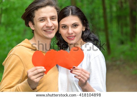 Happy couple in love a heart. Love couple hold red paper hearts.  - stock photo