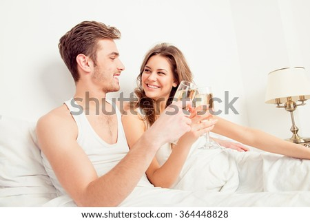 Happy couple in love at home embracing each other with champagne - stock photo