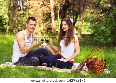 happy couple in love at picnic and drinking wine