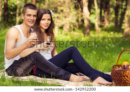 happy couple in love at picnic with glasses of wine - stock photo
