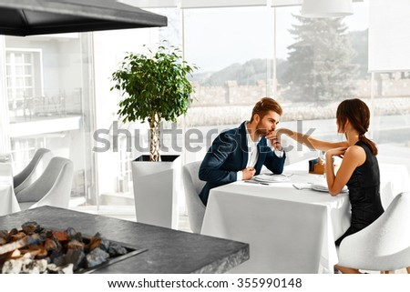 Happy Couple In Love Having Romantic Dinner In Gourmet Restaurant. Man Kissing Lovely Woman's Hand. Elegant People On A Date, Celebrating Anniversary Or Valentine's Day. Romance, Relationship Concept.